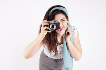 pinup style girl with red lips on a white background is holding an old reflex camera
