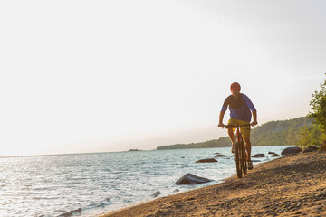Man riding a mountain bike on the beach