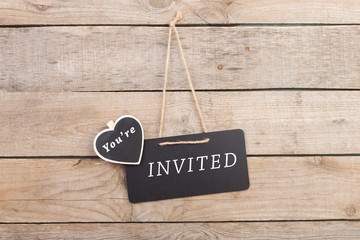 """Blackboards with text """"You're invited"""" on wooden background"""