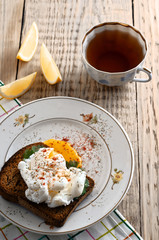 eggs pashot on a toast and tea with lemon on a wooden table