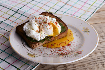 eggs pashot on a toast on a wooden table