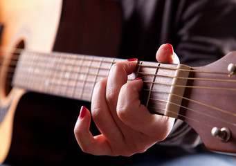 Close-up of woman playing acoustic guitar