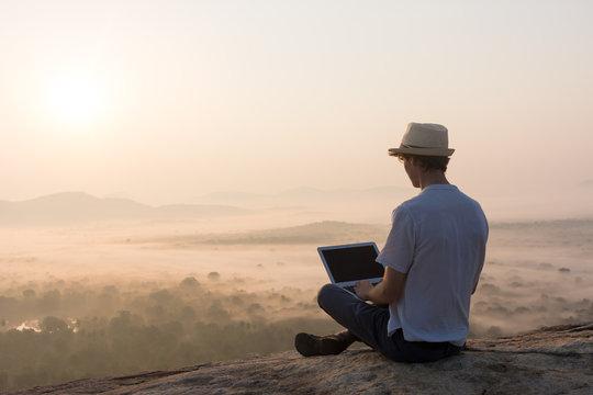 Homme et ordinateur au lever du soleil
