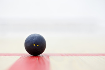 closeup of squash ball on the court