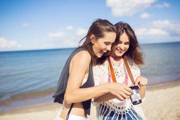 Beautiful women standing on beach watching photos on camera laughing