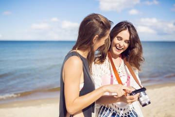 Happy women standing on beach watching photos on camera