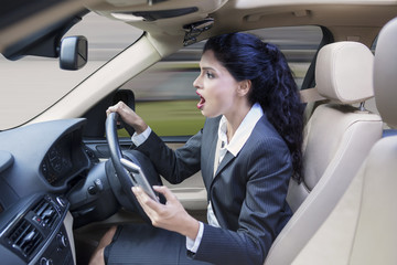 Female worker with cellphone driving car