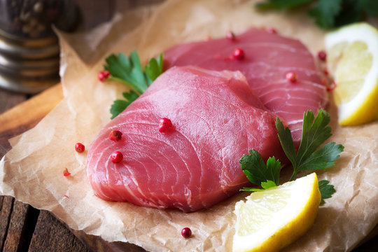 Fresh raw tuna steaks on parchment paper with pink pepper corns, parsley and slices of lemon