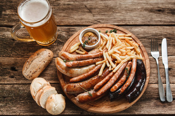 Traditional German food. Mug with beer and delicious grilled sausages and french fries served with bread buns on rustic wooden table in bar, top view.