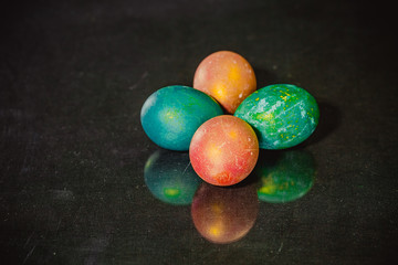 Red and green Easter eggs on dark background.
