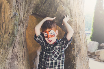 Boy child outdoors sit in tree with face painting