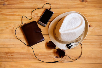 Hat, wallet, smartphone, headphones  and sunglasses on wooden background. Relaxation or vacation concept
