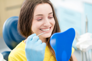 Young happy woman client looking at the mirror with toothy smile at the dental office