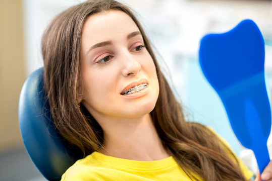 Worried woman smiling with braces looking at the mirror at the dental office