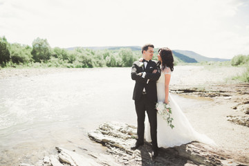 Elegant stylish happy brunette bride and gorgeous groom on the background of a beautiful waterfall in the mountains