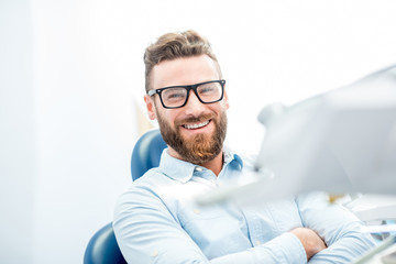 Handsome businessman with great smile sitting on the dental chair