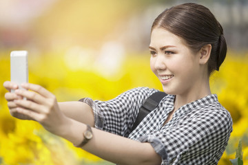 woman smiling while taking selfie picture with mobile phone in sunflowers field