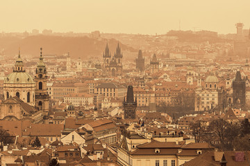 Prague historical sights, Charles bridge and old town, in misty winter day. Antique sepia retro filter.