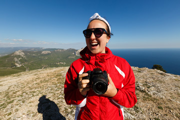 Happy woman photographer smiles on a peak of a mountain with dslr camera in her hands in mountains enjoying the climb with beautiful rocky and sea background