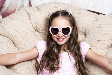 portrait of a little girl in pink sunglasses