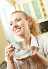 Young smiling woman drinking coffee, at home