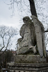 LVIV, UKRAINE - JANUARY 6, 2014: An old monument of angel at Lychakiv cemetery (Lviv, Ukraine) on winter cloudy day.