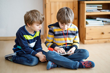 Two little kid boys reading a book at home