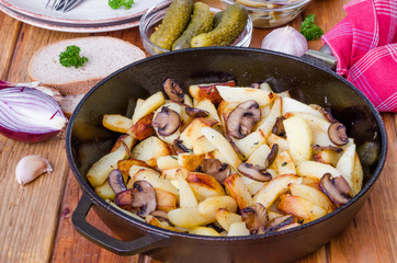 Fried potatoes with mushrooms in a pan on a wooden background