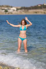 Girl in blue bikini comes from seawater