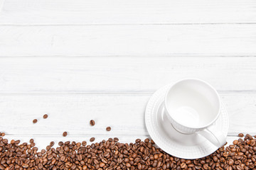 White Cup and coffee beans on the background. Copyspace for text.