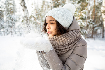 Portrait of happy girl blowing snow in winter