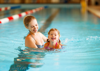 Mother teaches child to swim in pool