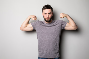 young man with relief muscles in jeans in shirt on a gray background