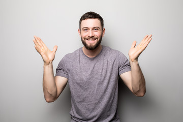 portrait of happy man rise up hands and successful achievement of goals on grey