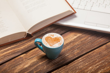 photo of beautiful cup of coffee, notebook and laptop on the wonderful brown wooden background