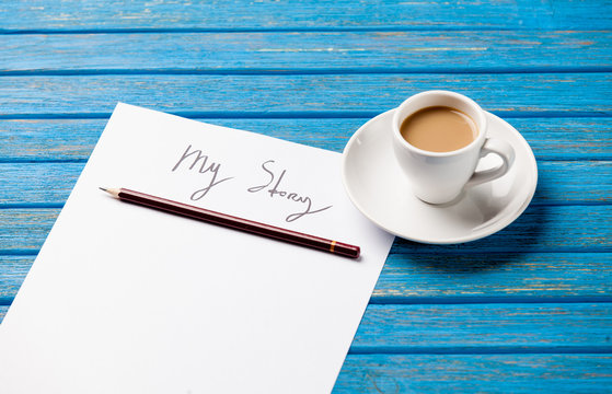 photo of paper My story and cup of coffee on the wonderful blue wooden background