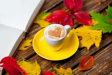 photo of cup of coffee, opened notebook and autumn leaves on the wonderful brown wooden background