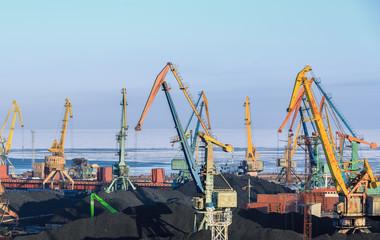 Портальные краны перегружают уголь в порту на судно