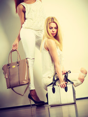 Two women in white clothes with bags handbags.