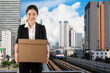 A young woman carrying a box with smile on city skytrain background