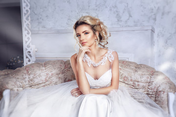 Beautiful bride posing in wedding dress sitting on sofa in a white photo Studio.