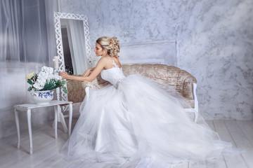 Beautiful bride posing in wedding dress sitting on sofa in a white photo Studio.
