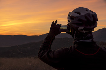 Man taking sunset sky picture on the mountain at sunset