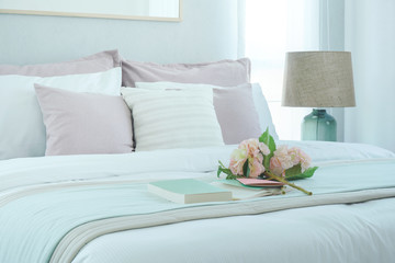 Romantic style bedroom interior with flower and book on bed
