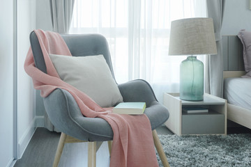 Gray easy armchair with pink scarf, pillow and book next to bed in the bedroom