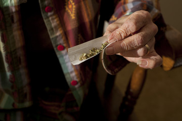 Close up of senior woman's hand rolling joint