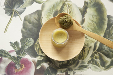 Overhead view of cannabis balm with wooden spoon and plate