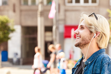 Hipster man standing on city street listening music