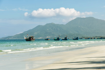 Fishing boats in the vietnams port. Beautiful tropical beach, white sand, clear blue and green water, mountains  on background