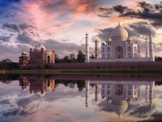 Fototapete - Taj Mahal at sunset with vibrant sky and reflections on the water of the Yamuna river. Photograph taken from Mehtab Bagh Agra.